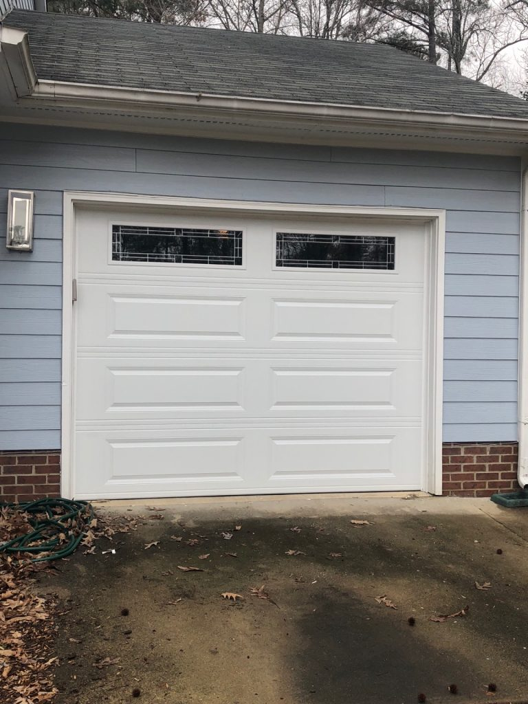single garage door on blue house
