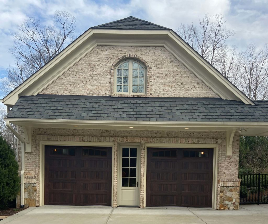 two wood tone stamped carriage garage doors