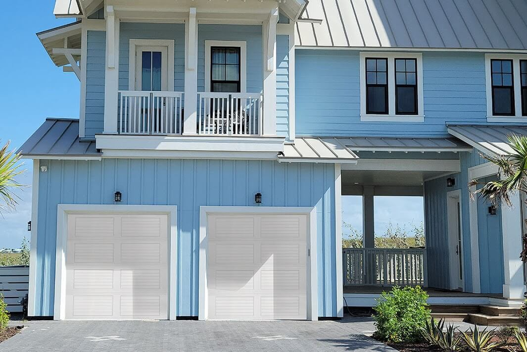 A blue house with white louvered garage doors